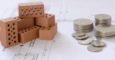 Imagem de tijolos ao lado de moedas