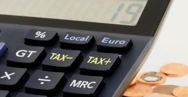 Imagem de uma calculadora perto de moedas