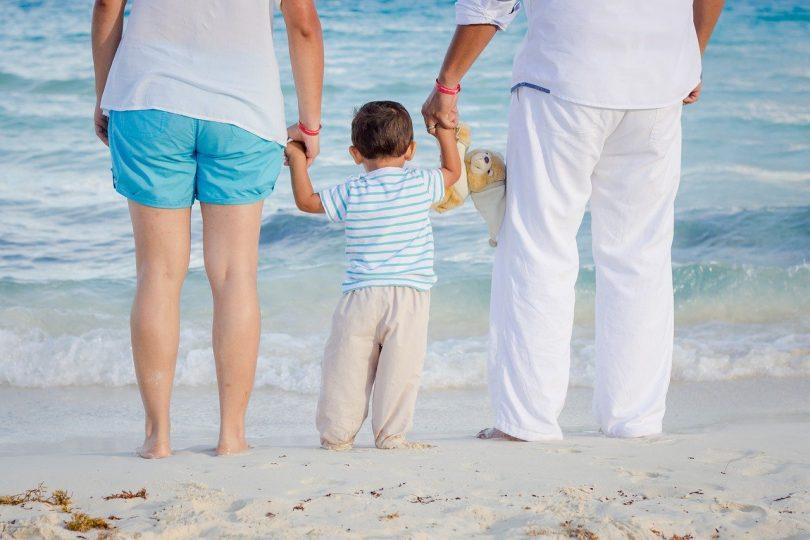 Famíia com jovem filho observando o movimento das ondas do mar