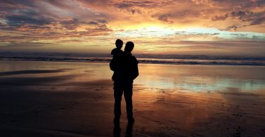 Pai e filho observam as cores do entardecer numa praia