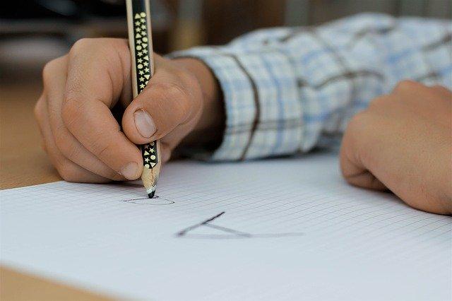 Criança escreve letras em seu caderno
