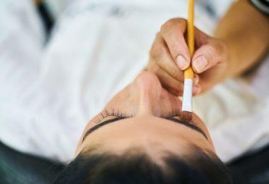 Mulher sendo maquiada nos olhos com um pincel