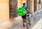 Homem carrega a caixa do Uber Eats enquanto faz entrega