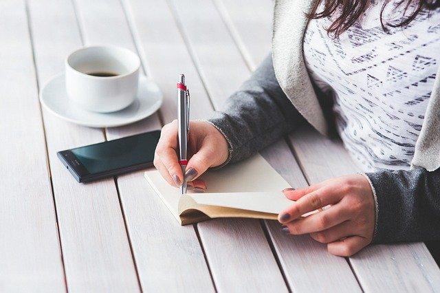 Mulher escrever algumas anotações no seu caderno