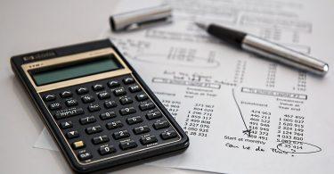 Calculadora em destaque ao lado de uma caneta