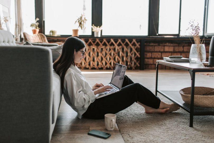 Estudante sentada em seu apartamento com um notebook